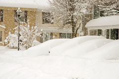 Cars and houses in blizzard. Cars and houses in deep snow during a winter blizzard royalty free stock image