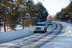 Cars on an ice city winter road. With trees around Royalty Free Stock Photo