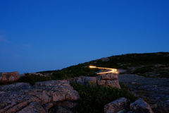 Cars leaving the top of Cadillac Mountain after sunset with ligh Royalty Free Stock Images