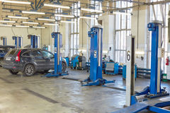 Cars and lift equipment in workshop Royalty Free Stock Images