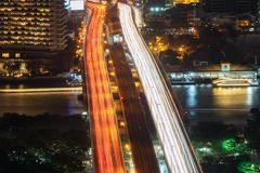 Cars light long exposure on Taksin Bridge in transportation concept. Train, boats lights with Chao Phraya River in Sathorn stock photography