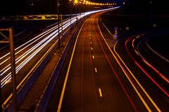 Cars light trails on a curved highway at night. Night traffic trails. Motion blur. Night city road with traffic headlight motion. Cityscape. Light up road by royalty free stock photo