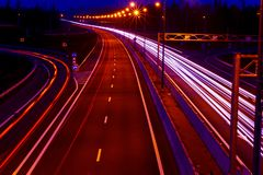 Cars light trails on a curved highway at night. Night traffic trails. Motion blur. Night city road with traffic headlight motion. Cityscape. Light up road by royalty free stock image