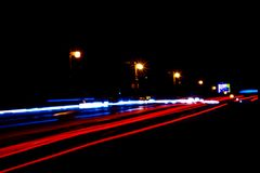 Cars light trails on a curved highway at night. Night traffic trails. Motion blur. Night city road with traffic headlight motion. Cityscape. Light up road by royalty free stock images