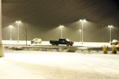 Cars, Lights and a Snowstorm. A few cars are sitting in the middle of a parking lot in the middle of a snowstorm Stock Photo