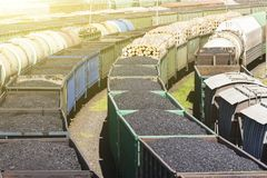 Cars with a load of coal and wood, the train carries coal, wood, fuel. Transport company. Cars with a load of coal and wood, the train carries coal, wood, fuel Royalty Free Stock Photo