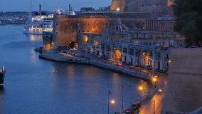 Cars motion along waterfront in Valletta - evening color changing time lapse stock video