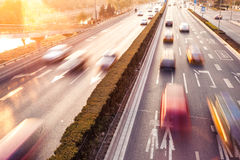 Cars in motion blur on street during sunset Stock Photos