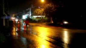 Cars and motorbikes driving on a wet road at night stock video footage