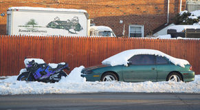 Cars and motorcycle under snow in Brooklyn after massive winter storms strikes Northeast Royalty Free Stock Photo