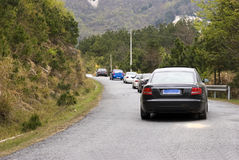 Cars in mountain road. A row of cars in a winding mountain road Stock Image