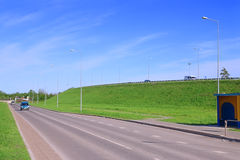 Cars move on asphalt road near hill in green grass Royalty Free Stock Images