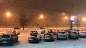 Cars move slowly along the road under heavy snow in the evening in lantern lighting. Snow-covered cars are parked in parking lot. stock video footage
