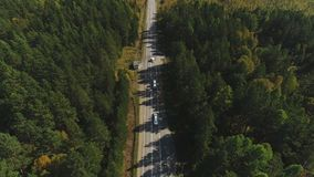 Cars moves along country road surrounded by green forest on sunny day. Cars moves along country road surrounded by green forest on sunny day, top view of stock footage