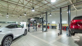 Cars moves on lifts in modern service station and men repair cars timelapse hyperlapse.