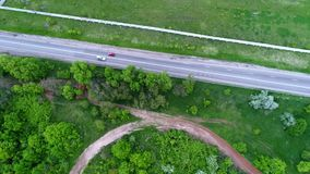 Cars on highway among fields, slow motion, aerial. Cars moving along the highway among green fields, some lonely trees, slow motion, aerial stock video footage