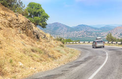 Cars moving along mountain road in Crimea. Cars moving along the curve mountain road in Crimea Royalty Free Stock Photo
