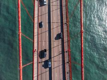 Cars moving on the asphalt road lanes on bridge above the water. View from the top. Royalty Free Stock Photos