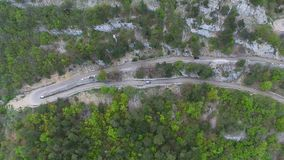 Cars Moving On A High Mountain Road. Aerial shot of the cars moving on a high mountain serpentine road at summer time stock footage