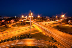 Cars moving through highway intersection at dusk. Leaving light trails Stock Photos