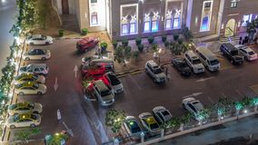 Cars moving on parking near Al Rahim Mosque in Dubai Marina aerial timelapse. Illuminated religious building between skyscrapers from above stock video footage