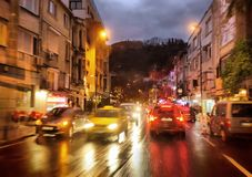 Cars and night traffic lights in rainy city. Night traffic in rainy city, shot from moving car, subjects blurred in motion Royalty Free Stock Photo