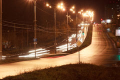 Cars and other transport drive on highway in the night city. Urban style Stock Image