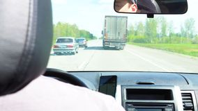 Cars overtake a truck. Cars overtake a truck on the road passing through the forest stock video footage