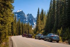 Cars park along the road to Moraine Lake in Canada. MORAINE LAKE, ALBERTA, CANADA - JUNE 27, 2017 : Cars park along the road to Moraine Lake in Banff National Royalty Free Stock Photography