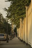 Cars parked along a quiet street opposite a tall wall topped wit stock photography
