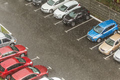 Cars parked at a parking lots near high-rise building under heavy shower rain and hurricane wind.  Royalty Free Stock Images