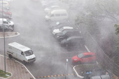 Cars parked at a parking lots near high-rise building under heavy shower rain and hurricane wind.  Royalty Free Stock Image