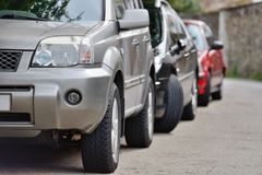 Cars parked in a row on a city street Stock Photography