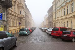 Cars parked on the side of the old residential street. Znojmo, Czech Republic, Europe. Cars parked on the side of the old residential street on a foggy winter Stock Image