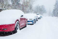 Cars parked and trapped under a deep blanket of snow in unexpected snow storm. Parked cars buried under a thick layer of snow from an unexpected snow storm Royalty Free Stock Image