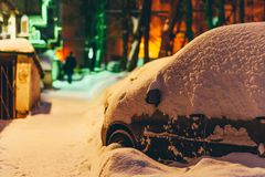 Cars stand in the yard in the evening covered with snow Royalty Free Stock Photos