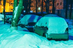 Cars stand in the yard in the evening covered with snow Royalty Free Stock Images