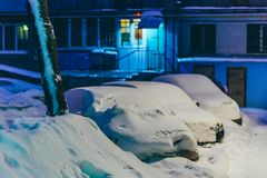 Cars stand in the yard in the evening covered with snow Royalty Free Stock Photo