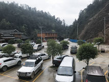 Cars on parking lot near gate of Dazhai Longsheng. DAZHAI, CHINA - MARCH 23, 2017: cars on parking lot near gate of Dazhai Longsheng village in spring. This is Stock Photo