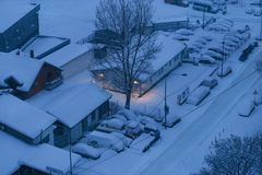 Cars on parking and street covered with big snow layer. View of winter and snowing on city street with snowflakes. In snowy season, motor vehicles with lot stock photography