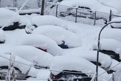 Cars on parking and street covered with big snow layer. View of winter and snowing on city street with snowflakes. In snowy season, motor vehicles with lot stock image