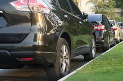 Cars parking in a tidy row in open area stock photography