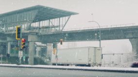 Cars Pass As Trucks Turn Off Highway In Snow Storm. Traffic near subway station with trucks and cars stock footage