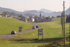 Cars pass by a countryside road, Affoltern im Emmental, Switzerland. Royalty Free Stock Photos