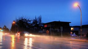 Cars Pass Houses In Dramatic Stormy Weather stock footage