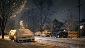 Cars Pass Houses At Night In Blizzard stock video footage