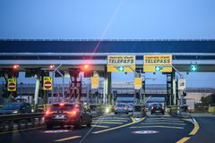 Cars pass through illuminated Telepass toll gates on Italian highway stock photos