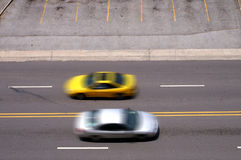 Cars Pass In Motion. Intentional blur of two speeding cars passing in motion Royalty Free Stock Photos
