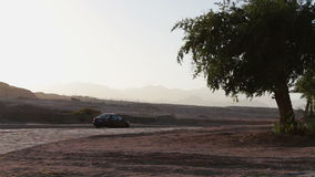 Cars pass by the picturesque road. Road in the Egyptian desert on a passing car on the background of the Sinai Mountains in the evening stock video footage