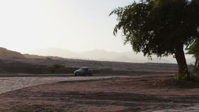 Cars pass by the picturesque road. Road in the Egyptian desert on a passing car on the background of the Sinai Mountains in the evening stock footage